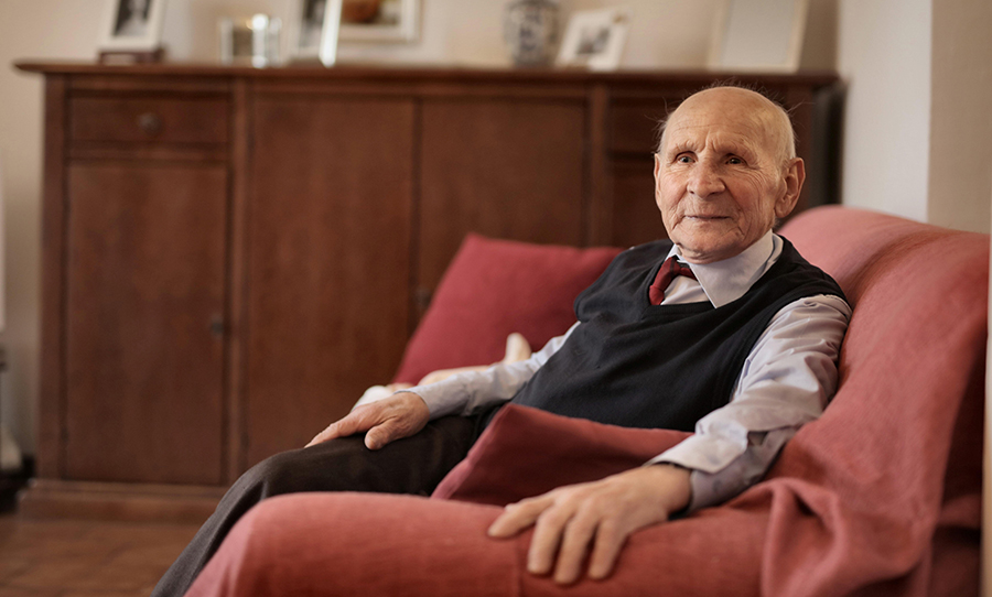 Older man on red sofa looking at the camera
