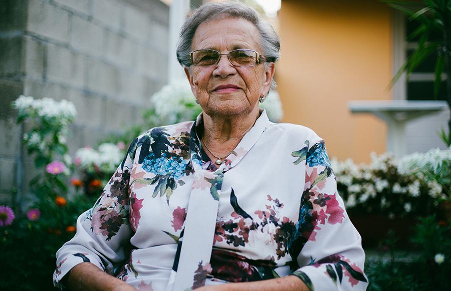 Older woman sitting in her garden outside